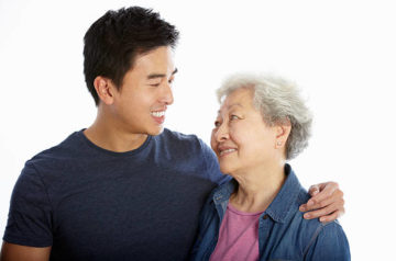 Studio Portrait Of Chinese Mother With Adult Son Smiling To Each Other